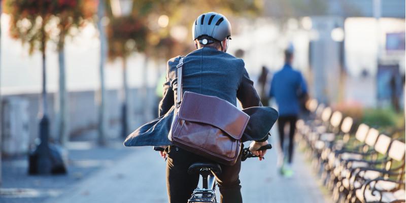 Fahrradfahrer mit Helm und Umhängetasche