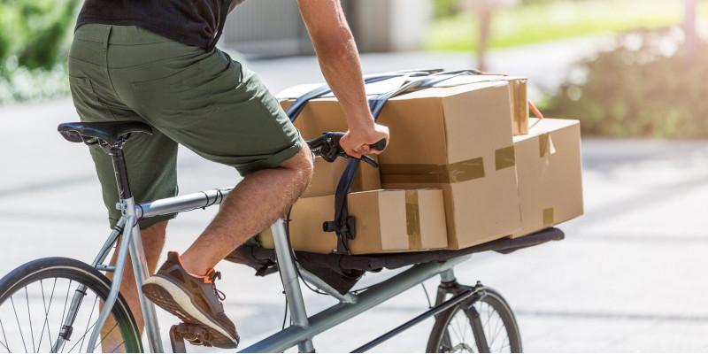 ein Fahrradkurier transportiert Pakete und Päckchen auf einem Lastenrad