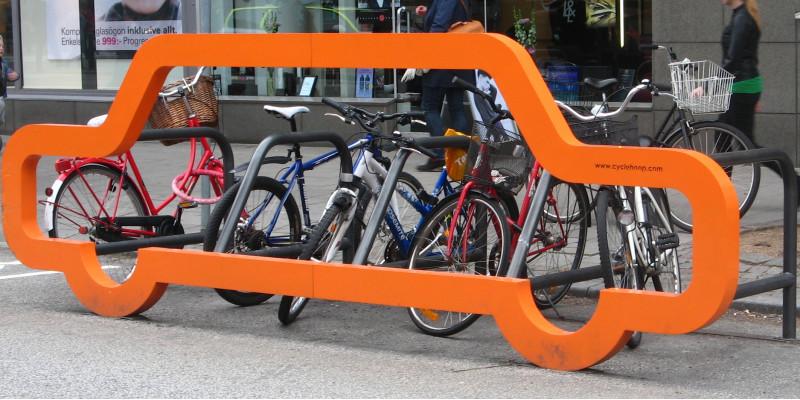 an der Front eines Fahrradständers für mehrere Räder in der Stadt ist ein lebensgroßer Umriss eines Autos angebracht und verdeutlicht: wo sonst nur ein Auto hinpasst, passen viele Fahrräder hin