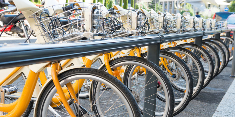 gelbe Leihfahrräder in einer Reihe in einem langen Fahrradständer