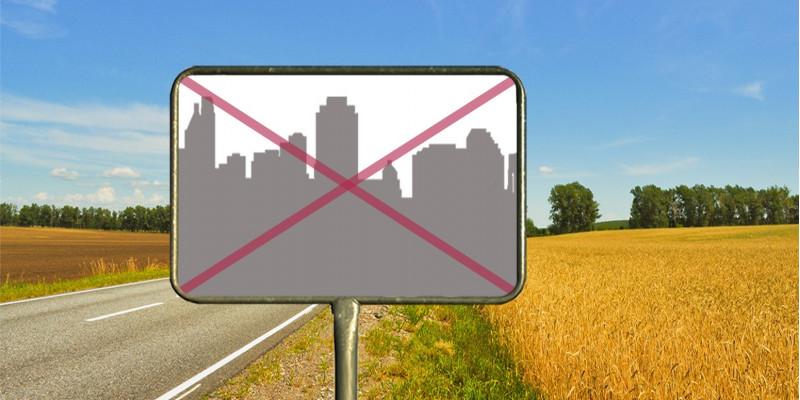 An einer Landstraße, die durch Felder führt, steht ein Ortsschild. Per Fotomontage ist in das Schild eine Stadtsilhouette mit vielen Gebäuden gemalt und diese ist rot durchgestrichen.