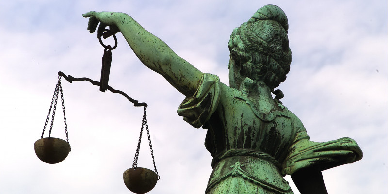 Bronze statue of Justitia, holding a pair of balances in her hand