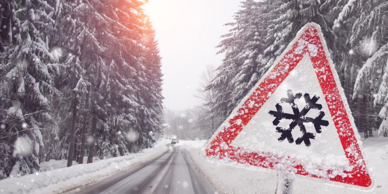 """verschneite Landstraße mit """"Achtung Glätte""""-Straßenschild"""