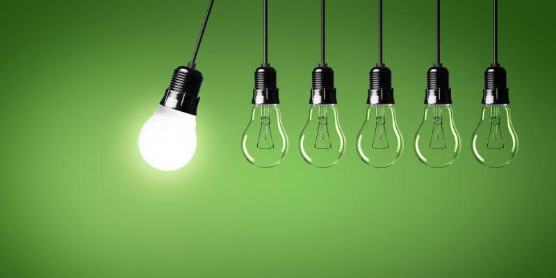 vor grünem Hintergrund schwingt eine leuchtende Energiesparlampe in einer Lampenfassung am Kabel gegen eine Reihe nicht leuchtender Glühlampen