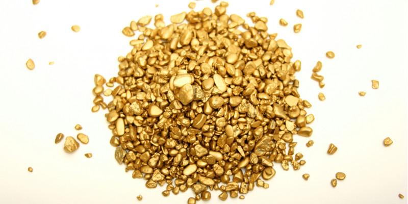 ein kleines Häufchen Goldklumpen auf einer weißen Unterlage
