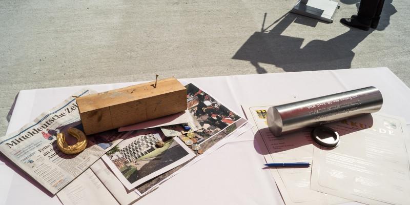 auf einem Tisch liegen eine Metallkapsel, eine Tageszeitung, Geldmünzen, Urkunden, Bauunterlagen und weitere Dokumente
