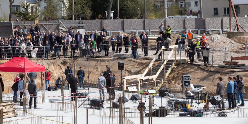 Blick von oben auf eine betonierte Bodenplatte, auf der ein Fest gefeiert wird. Viele Gäste stehen am Rand der Baustelle.