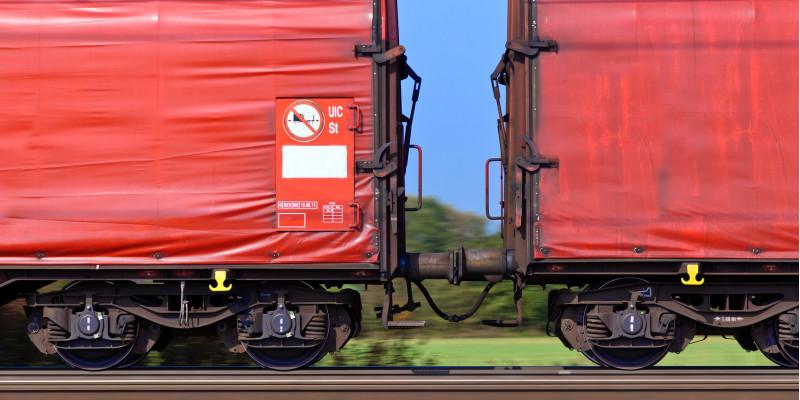 zwei rote Güter-Waggons auf der Schiene vor blauem Himmel und grüner Landschaft