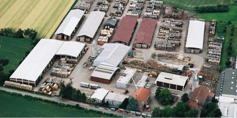 Betriebsgelände von oben fotografiert, zu sehen sind verschiedene Hallen und Lagerplätze, in der Mitte liegen Baumstämme