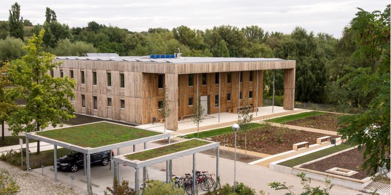 quadratischer, zweistöckiger Flachbau mit Holzfassade und Fahrradständerüberdachungen mit Dachbegrünung inmitten frisch angelegter und bepflanzter Außenanlagen