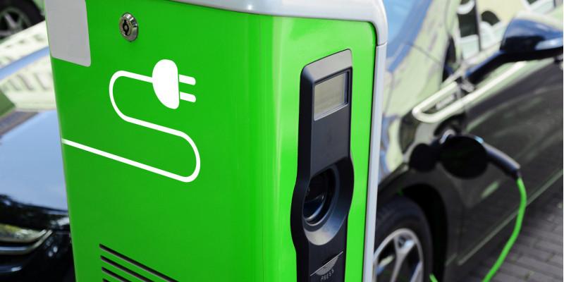 ein Elektroauto tankt Strom an einer grünen Ladesäule