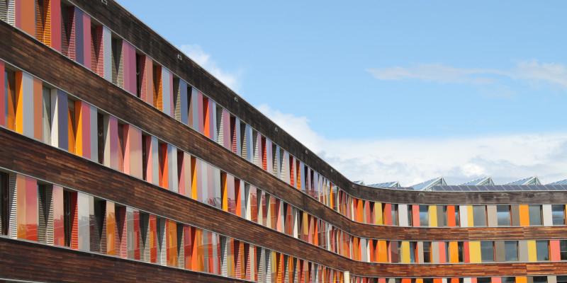 Rückwärtige Holz-Fassade des UBA Dessau-Roßlau mit Glasplatten in verschiedenen Rottönen