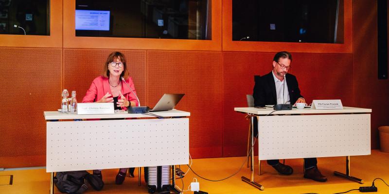 Prof. Christa Reicher und PSt Florian Pronold an jeweils einem Tisch mit Mikrofon und Namensschild