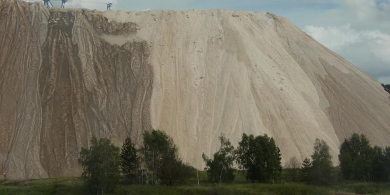 riesiger Haufen hellen Gesteins in der Landschaft, davor stehen einige Birken, die im Vergleich sehr klein wirken
