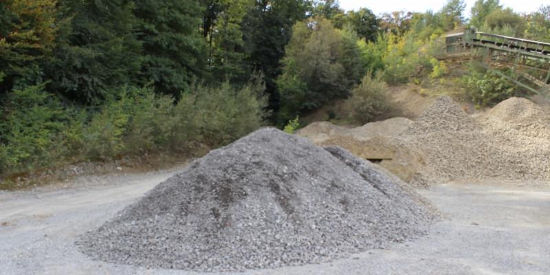 Im Vordergrund ein Haufen kleiner grauer Steine, im Hintergrund ein Haufen kleiner gelblicher Steine