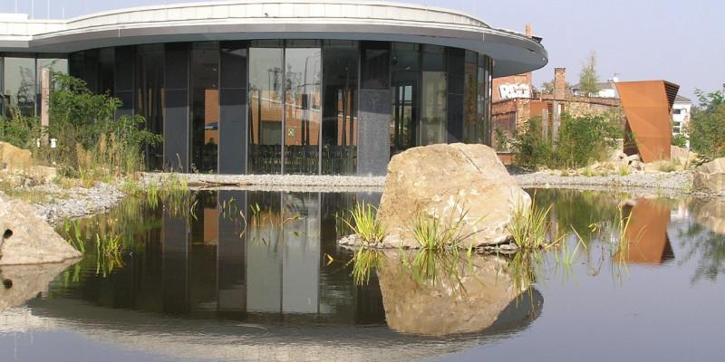 Niedriges, rundes Gebäude mit Glasfassade spiegelt sich in einem Teich mit Natursteinen