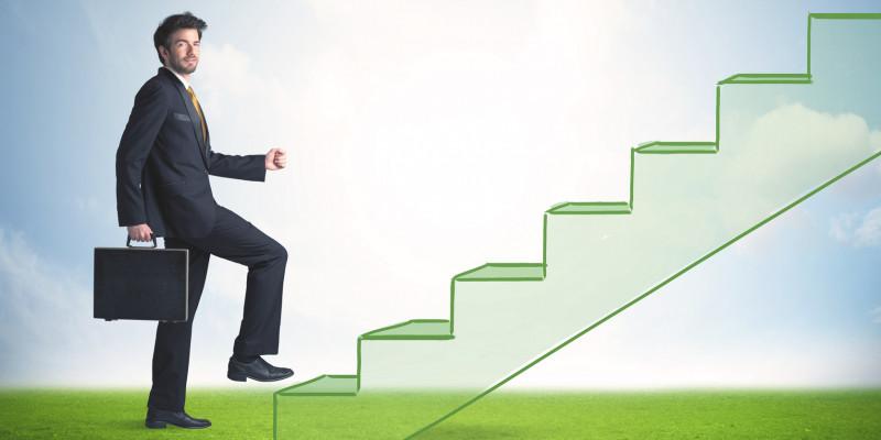 Fotomontage: ein junger Mann im Anzug und mit Aktentasche steigt eine grüne Treppe hinauf, die vom Rasen in den bolauen Himmel führt