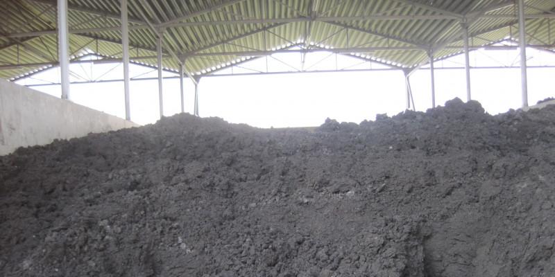 erdartige, dunkelgraue Masse türmt sich in einem überdachten Lagerplatz