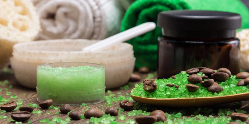 Kosmetiktiegel und Handtücher mit grünen Kügelchen und Kaffebohnen auf einer Holzoberfläche arrangiert