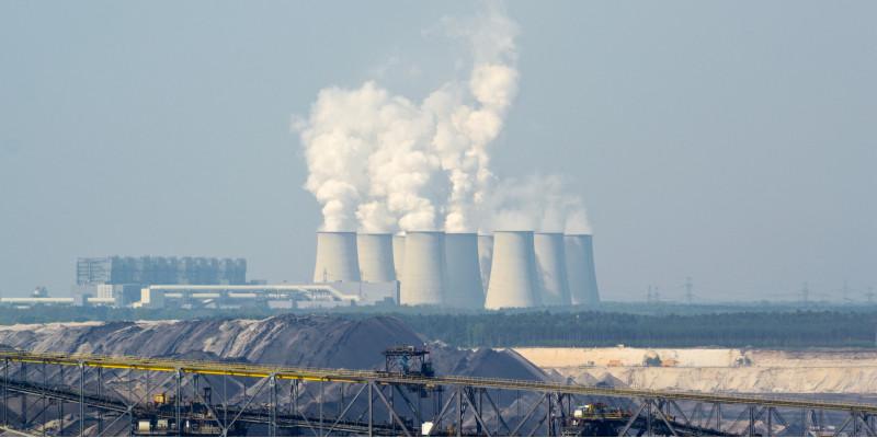 Braunkohletagebau und Kraftwerk mit dampfenden Kühltürmen