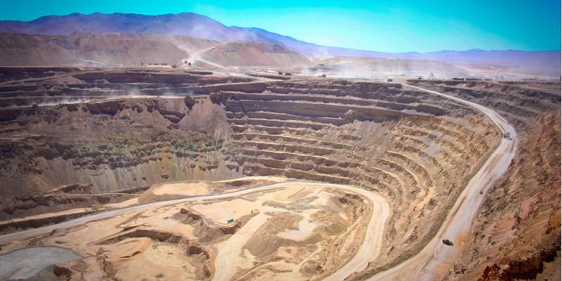 in einer bergigen, trockenen Landschaft klafft ein riesiges tiefes Loch mit terrassenförmigen Plateaus in der Erde