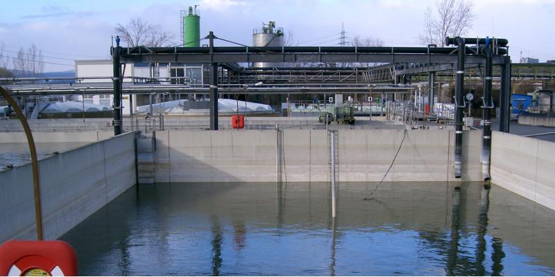 wassergefülltes, quadratisches Betonbecken vor einer Industrieanlage