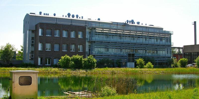 Dreistöckiges, langgezogenes modernes Bürogebäude, davor ein Fluss oder Kanal mit grasbewachsenen Ufern