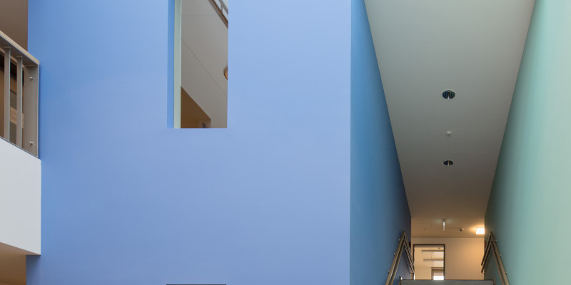 kleine Eingangshalle mit Glasdach und Treppenaufstieg, die Wände sind weiß, die Wände des Treppenhauses jedoch links blau uns rechts hellgrün gestrichen