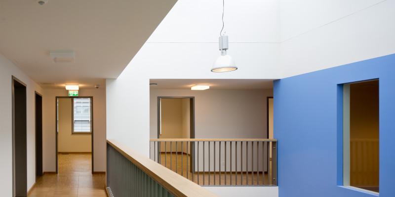 Flure mit Holzfußböden auf einer Galerie, weiße und blaue Wandflächen