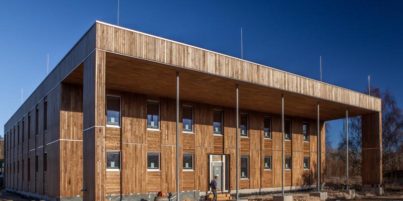 würfelförmiger, zweistöckiger Bau mit Holzfassade und Kollonadengang, davor ein Bauarbeiter, die Außenanlage noch ungestaltete Baustelle