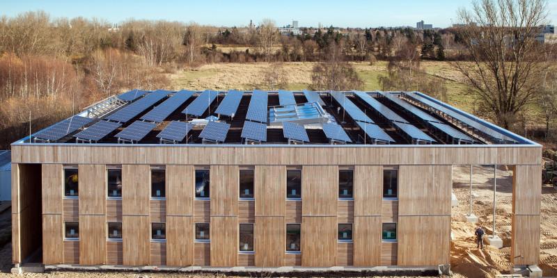 würfelförmiger, zweistöckiger Bau mit Holzfassade, auf dem gesamten Flachdach befinden sich leicht schräg aufgestellte Fotovoltaik-Elemente