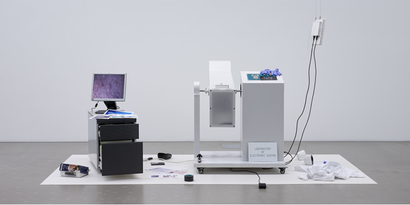 """Kunstobjekt in einem Ausstellungsraum: Auf einem Rollcontainer steht ein PC-Monitor mit einem unscharfen Bild, daneben ein Gerät mit Schild """"Laboratory of Electronic Ageing"""". Auf dem Boden liegen verstreut Ausdrucke, eine Rolle Klebeband und andere Objekte."""