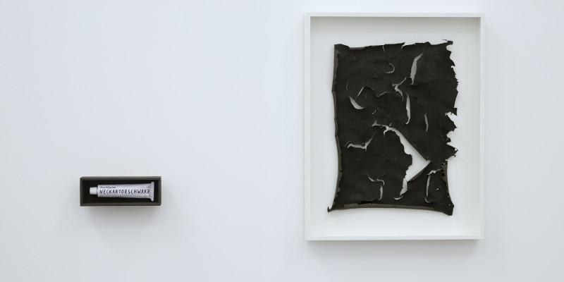 """an einer weißen Wand hängt eingerahmt ein kohlrabenschwarzes, zerrissenes Blatt Papier oder Haut, daneben hängt, schwarz eingerahmt, eine Tube mit der Aufschrift """"Neckartorschwarz"""""""
