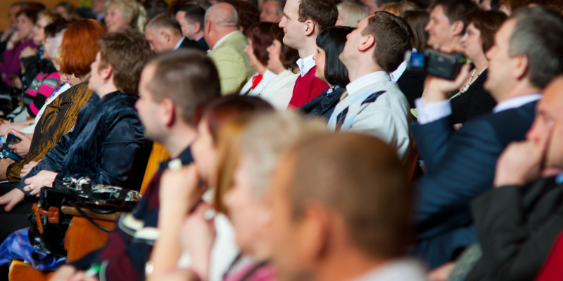 Zuhörer sitzen in einem Veranstaltungssaal in Stuhreihen