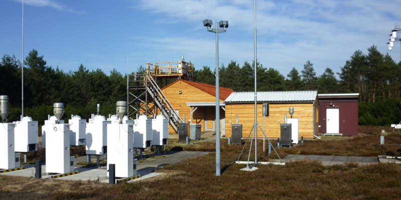 Outdoor observation area, two small buildings of light-coloured wood in the background