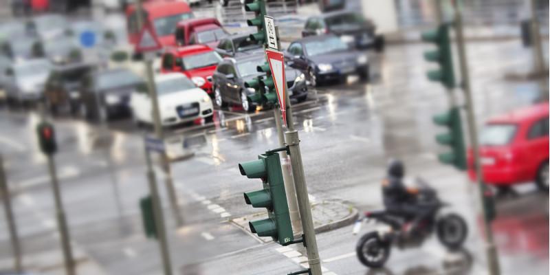 dicht befahrene Straßenkreuzung mit Ampeln, Autos und Motorrad