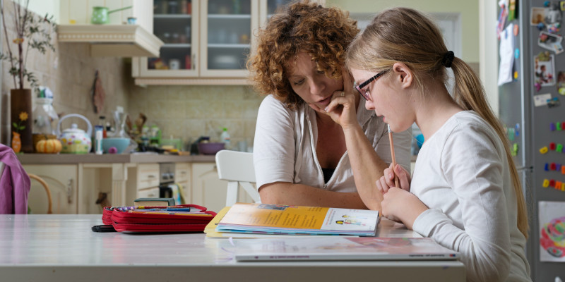 Mutter und Tochter sitzen am Küchentisch über einem Lehrbuch
