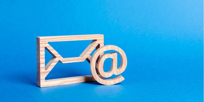 symbolischer Briefumschlag und @-Zeichen aus Holz vor blauem Hintergrund