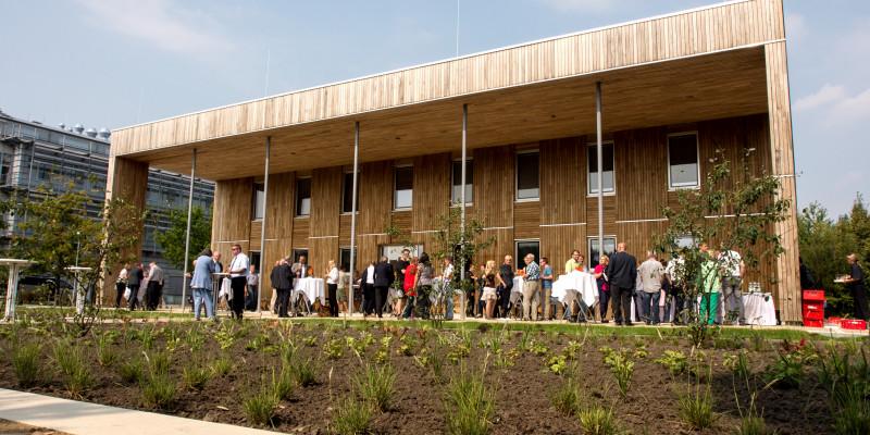 zweistöckicker Flachbau mit Holzfassade, unter einem Vordach stehen Menschen an Tischen, essen, trinken und unterhalten sich, im Vordergrund ein frisch bepflanztes Beet