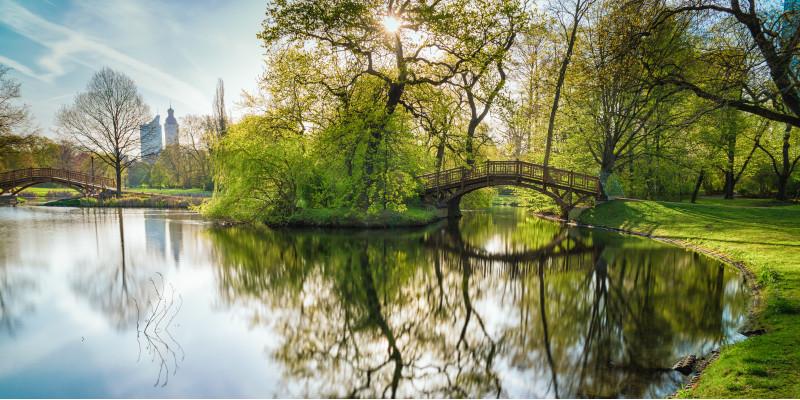 in einem Park spiegeln sich Bäume und eine Brücke in einem Teich, im Hintergrund Gebäude einer Großstadt