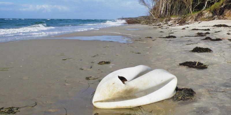 an einem Sansstrand am Meer liegt ein weißer Gegenstand, der einem Schwan ähnelt, aber ein kaputter weißer Gymnastikball oder ein ähnlicher Kunststoffgegenstand ist