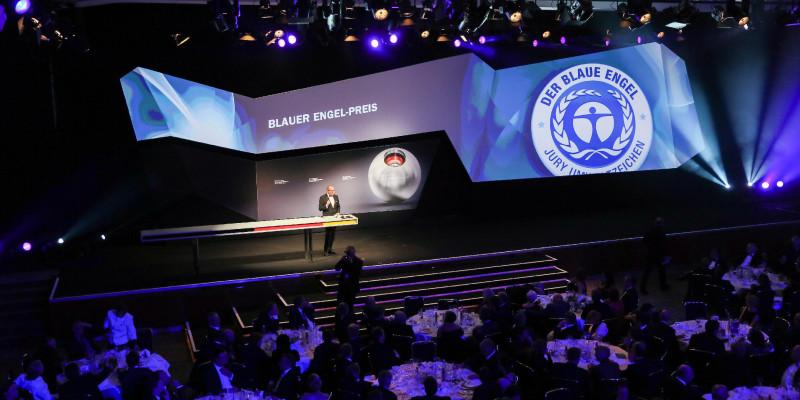 """in einem Saal steht ein Sprecher auf der Bühne, im Hintergrund ist das Logo """"Blauer Engel"""" und der Schriftzug """"Blauer Engel-Preis"""" zu sehen"""