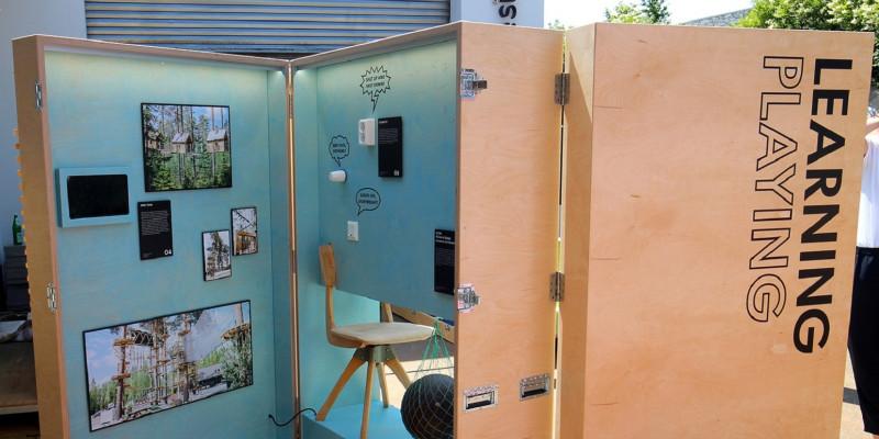 mannshohe Ausstellungsbox aus Holz auf Rollen, aufgeklappt sind Exponate zu sehen