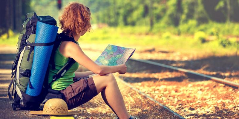 eine junge, sportlich gekleidete Frau mit Rucksack, Strohhut und Isomatte wartet auf der Bahnsteigkante in der Sonne sitzend auf einen Zug und schaut in eine Landkarte