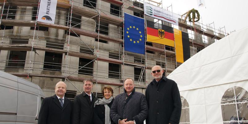 Gruppenfoto: vier Männer und eine Frau vor einem eingerüsteten Rohbau mit Richtkranz und Fahnen der EU, Deutschland, Sachsen-Anhalt, Bundesanstalt für Immobilienaufgaben und Partnerbau
