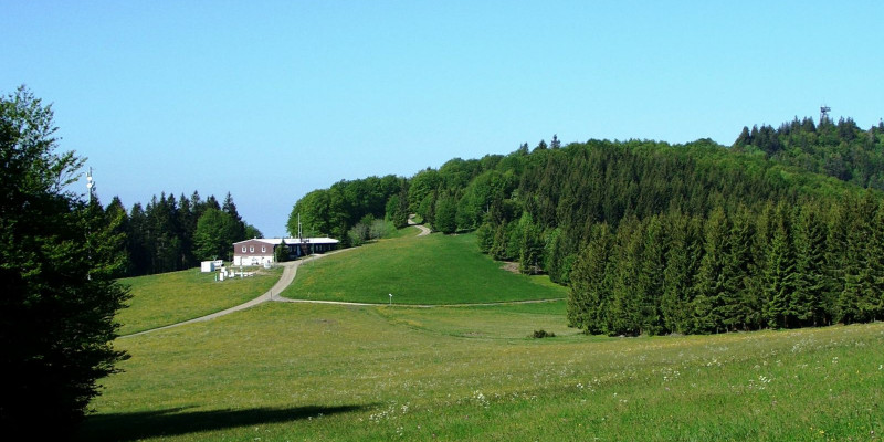 Building of the air quality measuring station in hilly landscape with fields and spruce forest