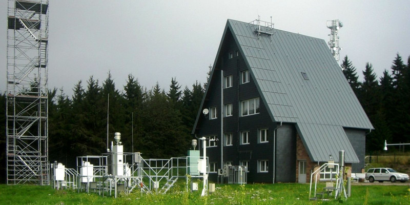 Small, four-storey building with dark brown wooden façade and gabled roof, with measuring devices on a field in front