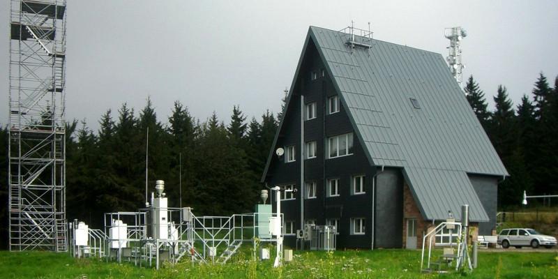 kleines vierstöckiges Gebäude mit dunkelbrauner Holzfassade und Satteldach bis zum Boden, davor Messeinrichtungen auf einer Wiese