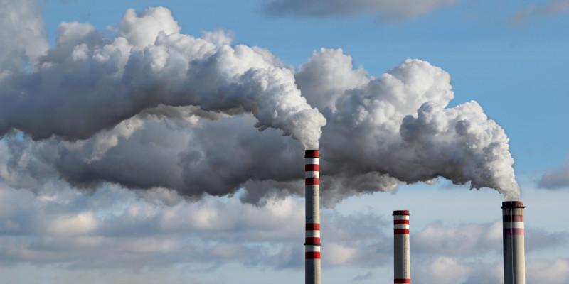 rauchende Industrie-Schornsteine vor einem bewölkten Himmel