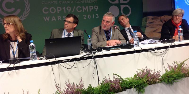 Jochen Flasbarth mit anderen Rednern auf einem Podium, im Hintergrund eine Stellwand mit dem Logo der Warschauerr Klimakonferenz COP19/CMP9